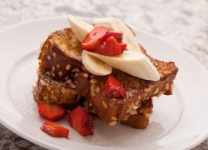 French toast topped with strawberries and bananas