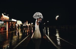 bride and groom sharing an umbrella in the rain on the boardwalk