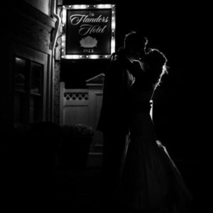 black and white photo of couple kissing outside The Flanders Hotel