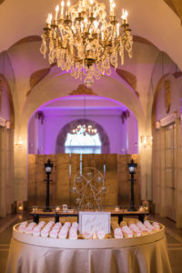 Hall of mirrors decorated with beachy placecard table and pink lighting