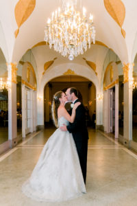 bride and groom kissing in the hall of mirrors